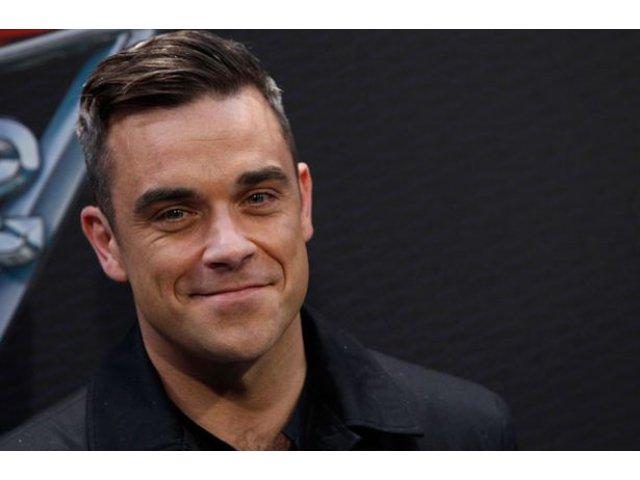 Robbie Williams, filmat in timp ce isi curata mainile cu gel antibacterian dupa ce a salutat fanii